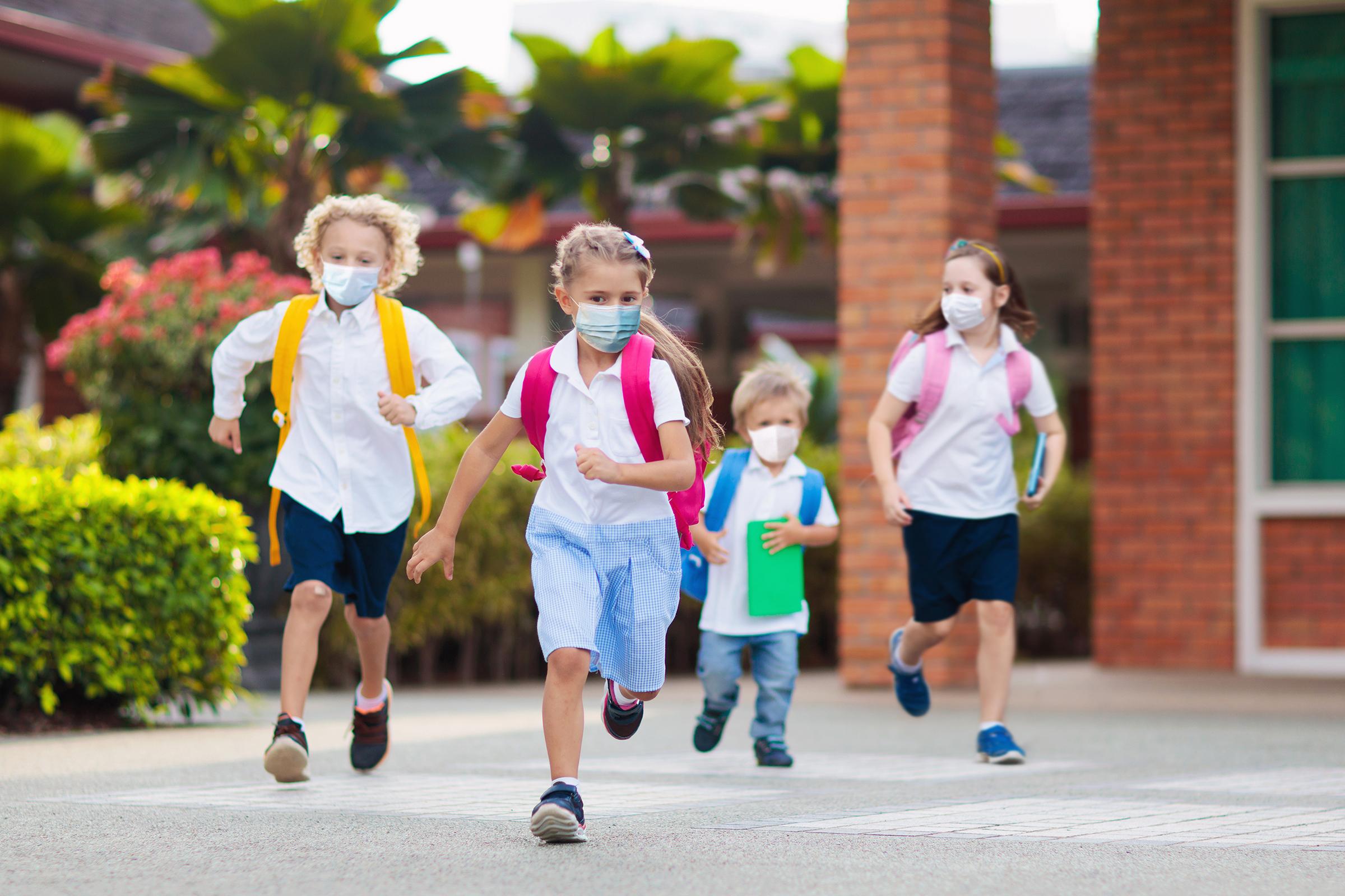 Children wearing masks playing at school