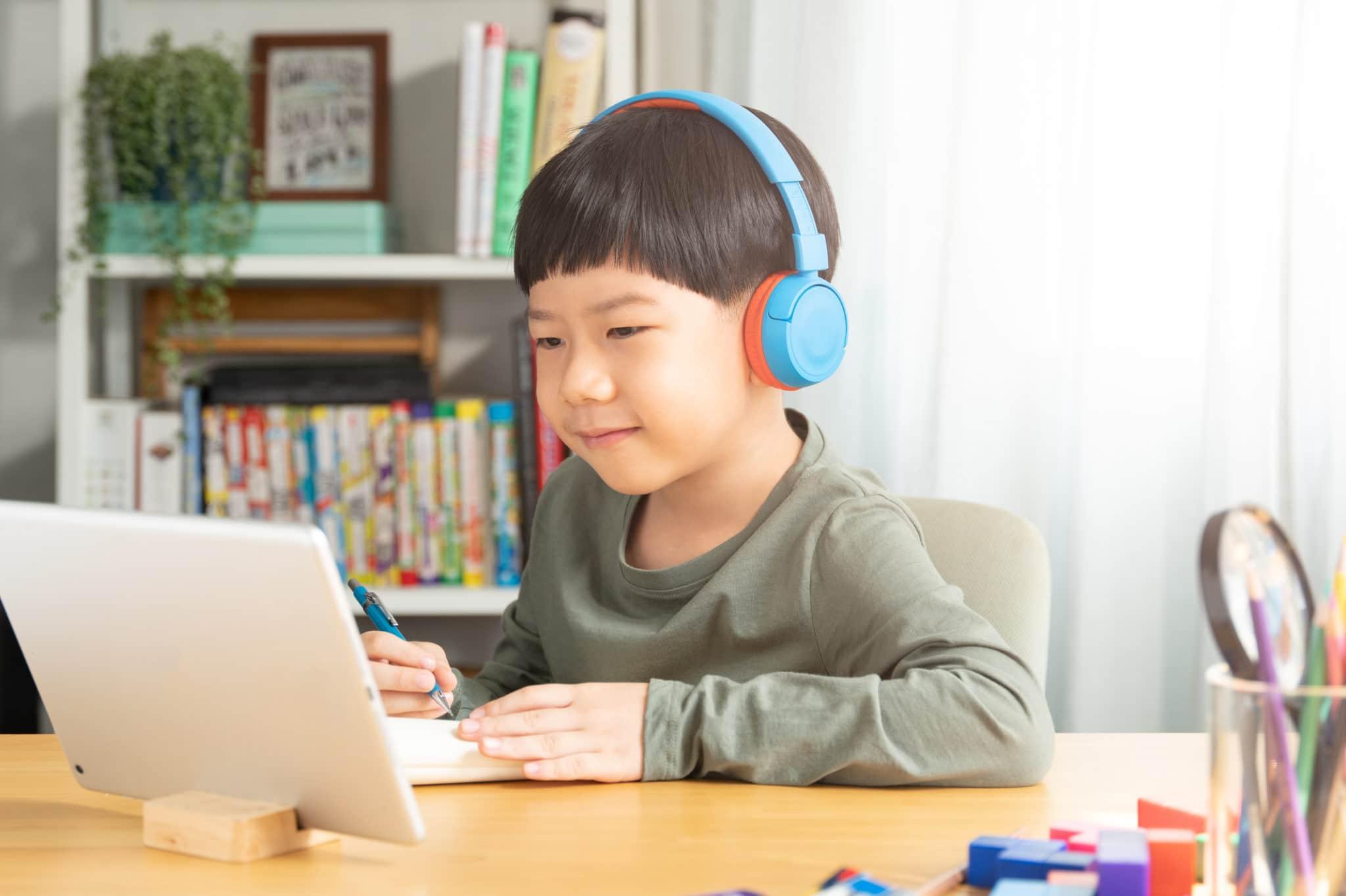 young boy smiles at computer
